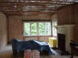 Woonkamer met monumentale schouw in een oud landhuis staat klaar op opnieuw te plafonneren tijdens de renovatie.