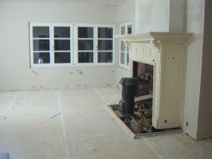 Woonkamer met monumentale schouw in een oud landhuis, die pas geplafonneerd is tijdens een renovatie.