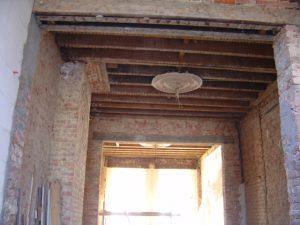Muren en balkenlaag in de woonkamer van een oude burgerwoning in ruwbouwfase tijdens een volledige renovatie. Klaar om te plafonneren en terug mouluren te trekken.