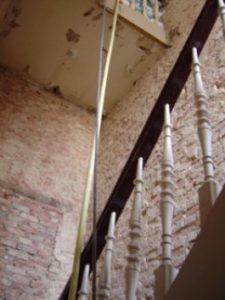 Muren in ruwbouw die klaarstaan om opnieuw te pleisteren tijdens de renovatie van een oude traphal.