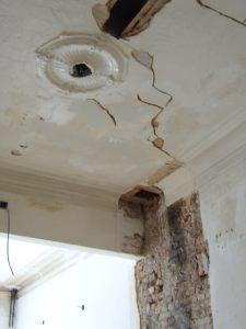 Een zwaar beschadigd oud plafond met mouluren en rosace in een burgerwoning staat klaar om te restaureren.