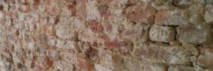 Detailbeeld van oud slecht metselwerk dat met bruine kalkmortel is gemetst.