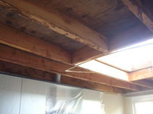 Roostering/balkenlaag van een keukenplafond met lichtkoepel na waterschade die klaar staat om opnieuw af te werken met gyproc.