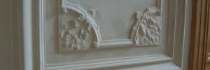 Mouluren en ornamenten op de muren in de gang in een oude meesterwoning.