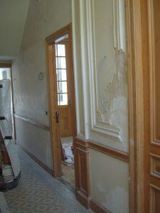 Beschadigde mouluren en kapot ornament op de muren van de gang in een oude meesterwoning.