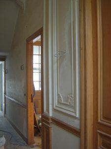 Gerestaureerde mouluren en nieuw ornament op de muren van de gang in een oude meesterwoning.