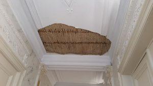 Stuk uit antiek plafond met mouluren gevallen in een gang