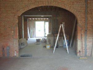 Een korfboog in oud metselwerk die klaarstaat om opnieuw te bepleisteren tijdens een renovatie.