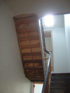 Onderkant van een houten trap waar de oude bruine kalkmortelbezetting en de houten latjes verwijderd zijn.