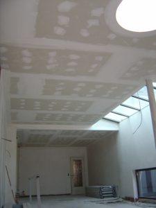 Afgewerkt gyprocplafond met een ronde lichtkoepel.