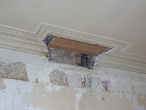 Stuk van een moulure op het plafond op de plaats waar de schouw is afgebroken.