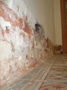 Onderkant van een oude binnenmuur met opstijgend vocht waarvan de onderkant van de bepleistering is afgekapt en geInjecteerd.