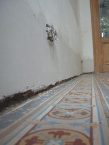 Oude binnenmuur met opstijgend vocht waarvan de onderkant van de bepleistering werd afgekapt en geïnjecteerd. Die onderste 30 centimeter werden opnieuw bepleisterd.