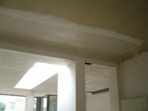Nieuwe bepleistering op de muren en gyprocplafond na de renovatie van een oude bel-etage woning.