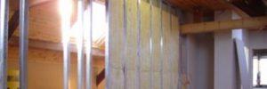 Een gegalvaniseerd latwerk metalstud met daarin glasvezelisolatie op zolder, klaar om er gyproc tegen te schroevn.