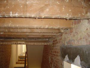 Balkenlaag van het plafond van een oude gang waartegen opnieuw gepleisterd gaat worden en afgewerkt met een moulure.