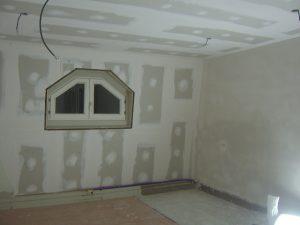 Nieuw afgepleisterde muren en gyprocplafond geplaatst in deze mansardekamer na renovatie.
