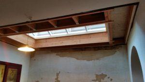 Vernieuwde balkenlaag van een plat dak met koepel en beschadigde muurbepleistering, klaar om te herstellen na waterschade en af te werken met gyproc.