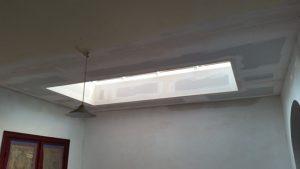 Nieuw afgewerkt gyprocplafond met lichtkoepel en herstelling pleisterwerk van de muren na vernieling door waterschade.