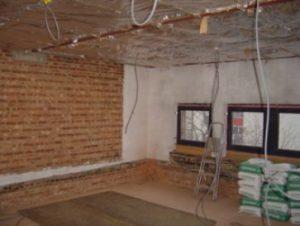 Oude buitenmuren en nieuwe balkenlaag in een woninguitbreiding staan klaar om geplafonneerd te worden
