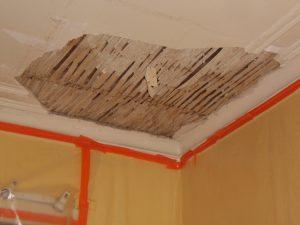 Oud plafond met mouluren op houten latjes beschadigd door wateroverlast. Er is een stuk uit het plafond gevallen.