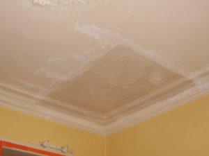 Oud plafond met mouluren hersteld na beschadiging door waterschade.