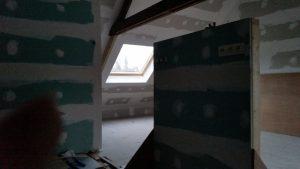 Schuin dak van een zolder, afgewerkt met isolatie en gyproc.