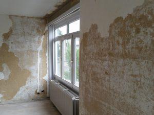 Oude bruine kalkmortelbepleistering is losgekomen bij verwijderen van het behangpapier.
