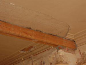 Oud plafond met zwaar beschadigde en ontbrekende mouluren.