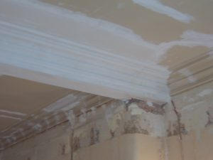 Volledig herstelde en gerestaureerde mouluren op een oud plafond.