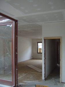 Verbouwing van een huis, binnenzicht in de leefkamer en de keuken na de plafonneer- en gyprocwerken.