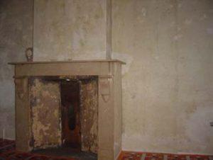 Beschadigde oude bruine bezetting waarover een nieuwe witte afwerklaag in gips zal aangebracht worden.