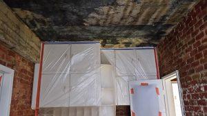 Ruwbouwfase in de renovatie van een keuken. Muren en plafond zijn afgekapt en staan klaar om opnieuw te pleisteren.