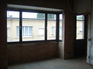 Slaapkamer met erker in ruwbouw tjdens renovatieproject. De oude bruine kalkmortel bepleistering is afgekapt.