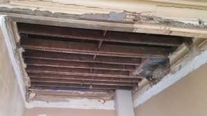 Totaal vernield oud plafond. De houten balkenlaag is nog zichtbaar. Enkel een paar stukken moulure zijn nog aanwezig.